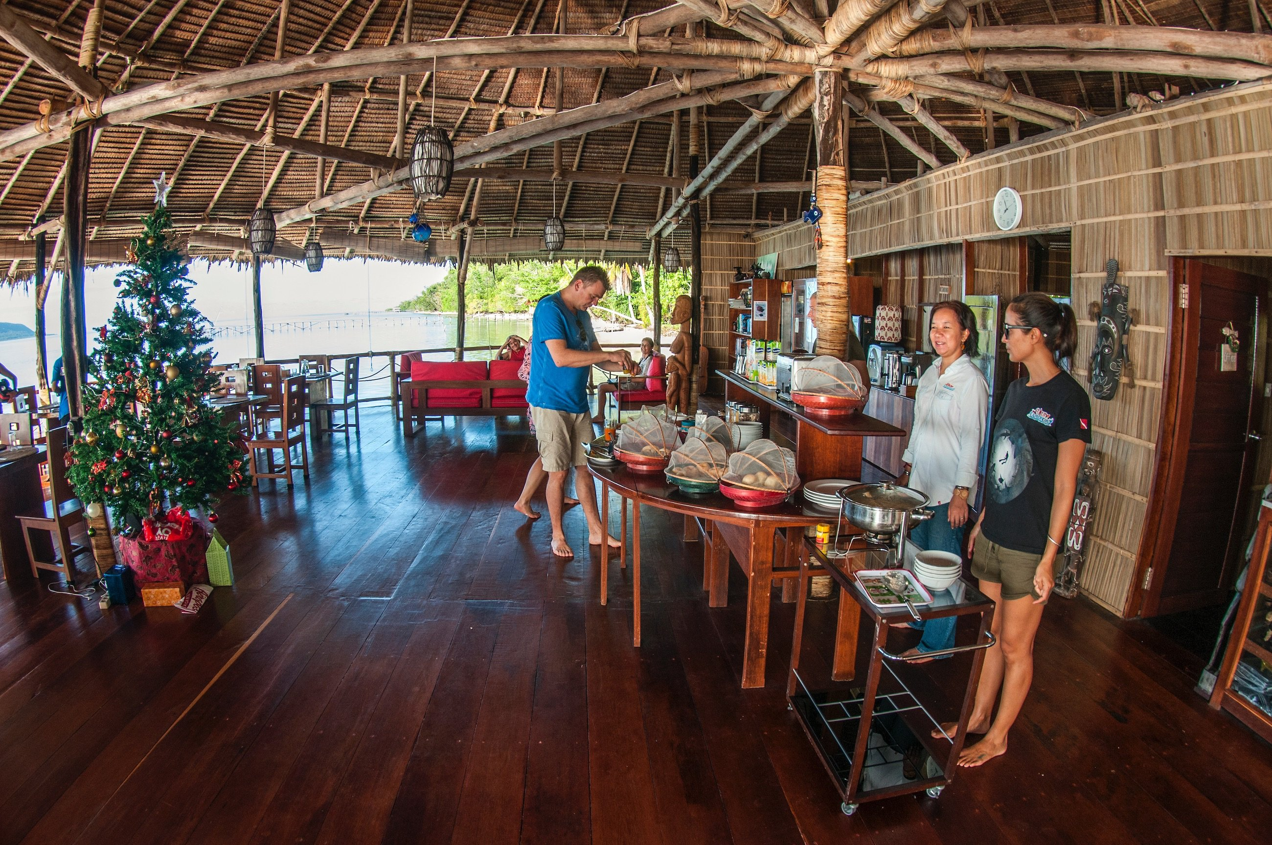 (English) guests enjoying the breakfast buffet overseen by our attentive staff in our restaurant built over the waters of Raja Ampat with a christmas tree