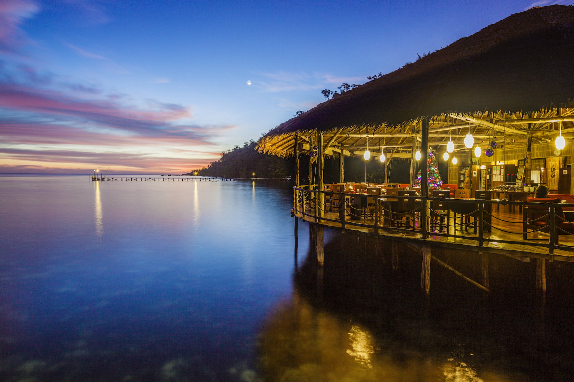 (English) ambiance of our restaurant in Raja Ampat with a colorful evening sky