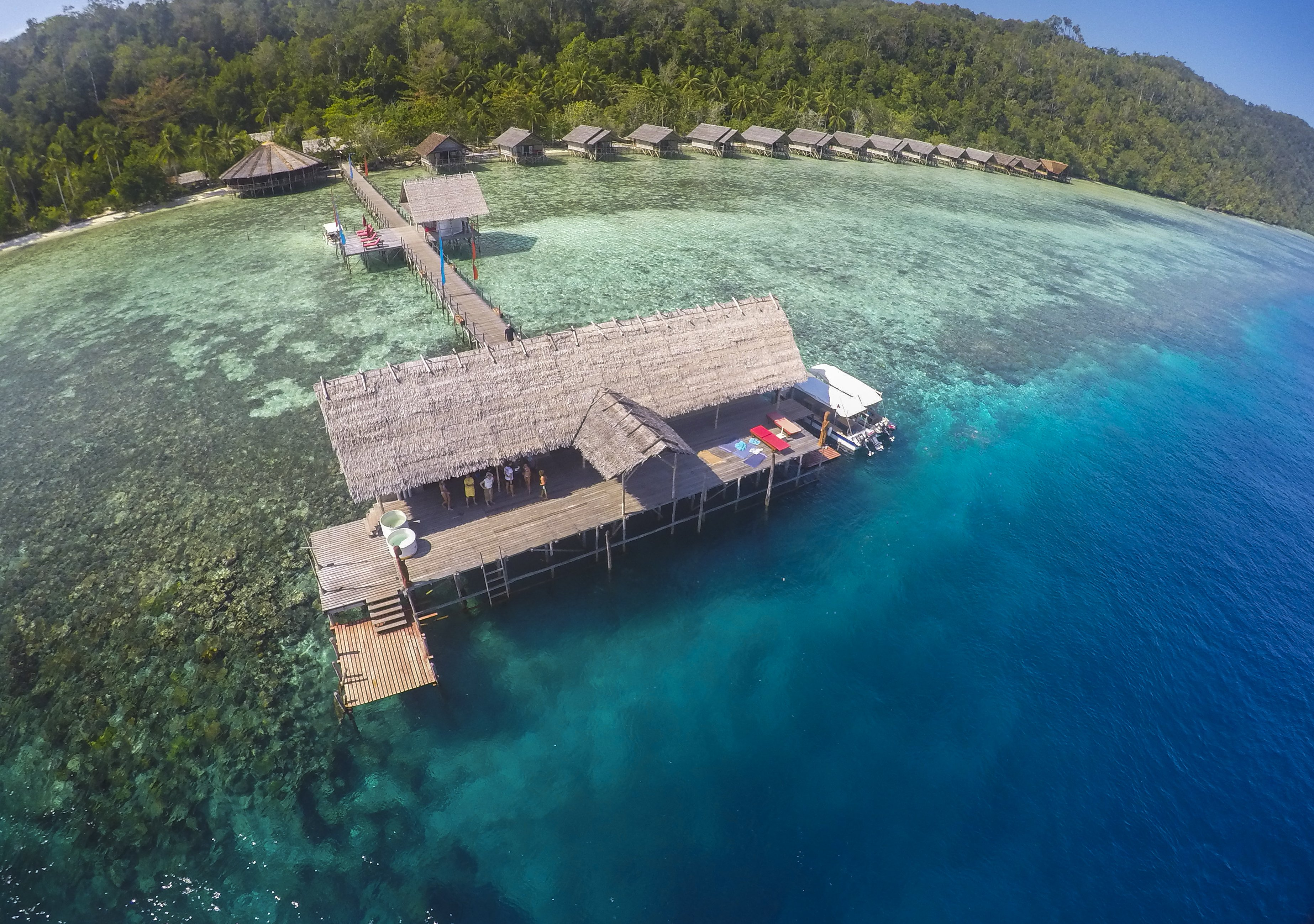 the dive centre building of Papua Explorers in an aerial shot with the water bungalows in the background
