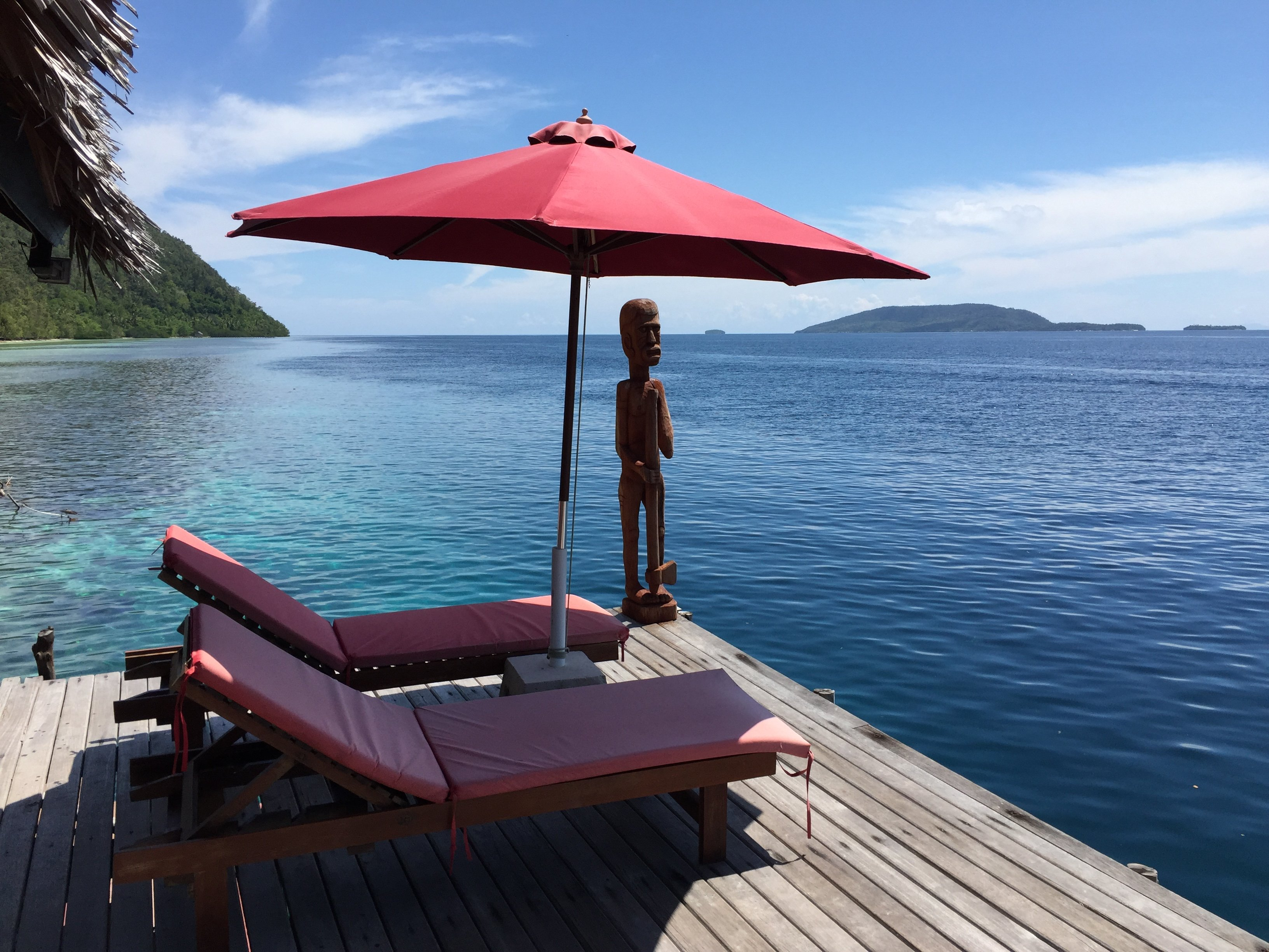 sunloungers and red umbrella and a wooden papuan statuse at our dive centre facing the ocean
