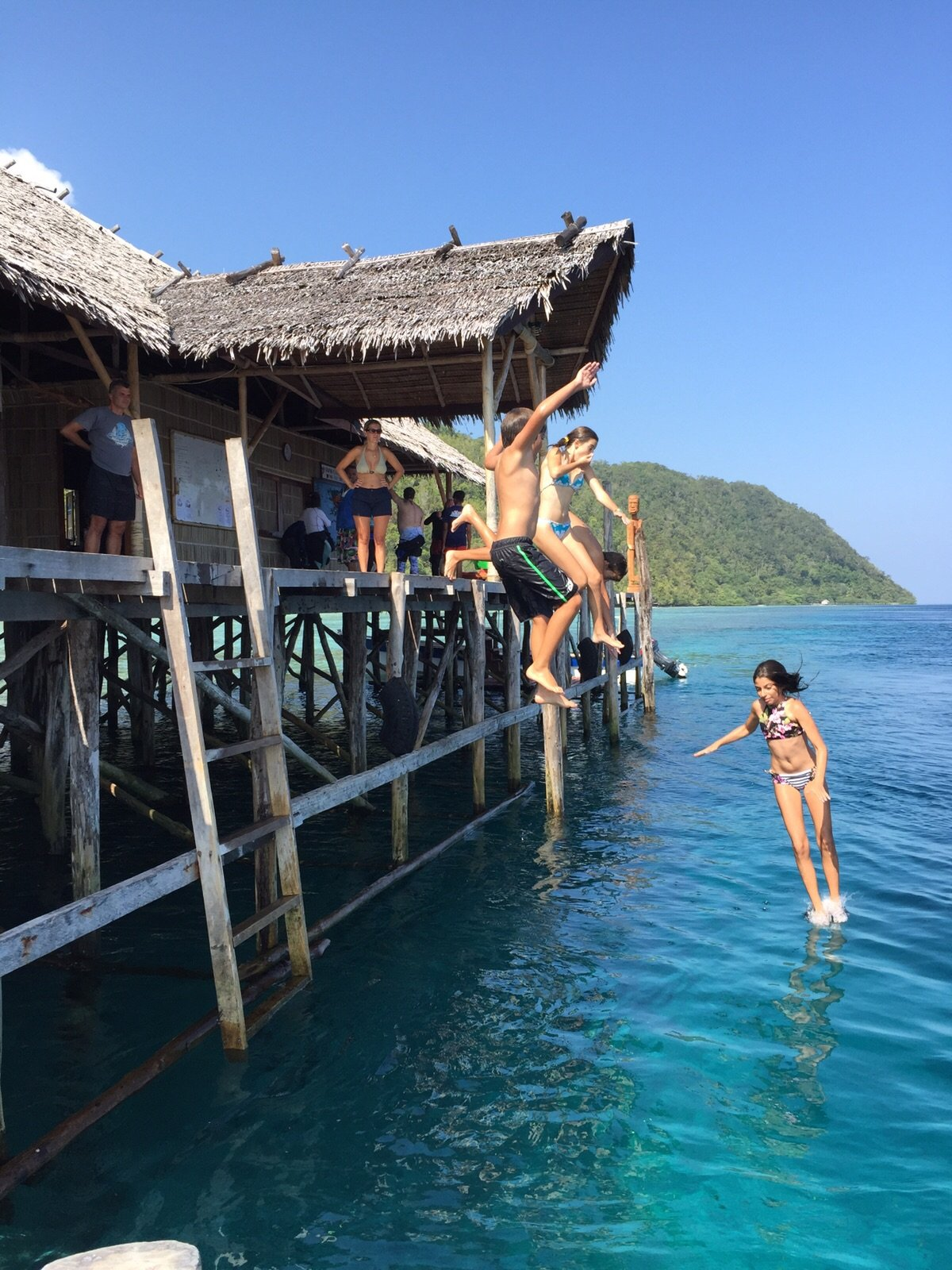 kids jumping into the water from the side of our dive center in Raja Ampat