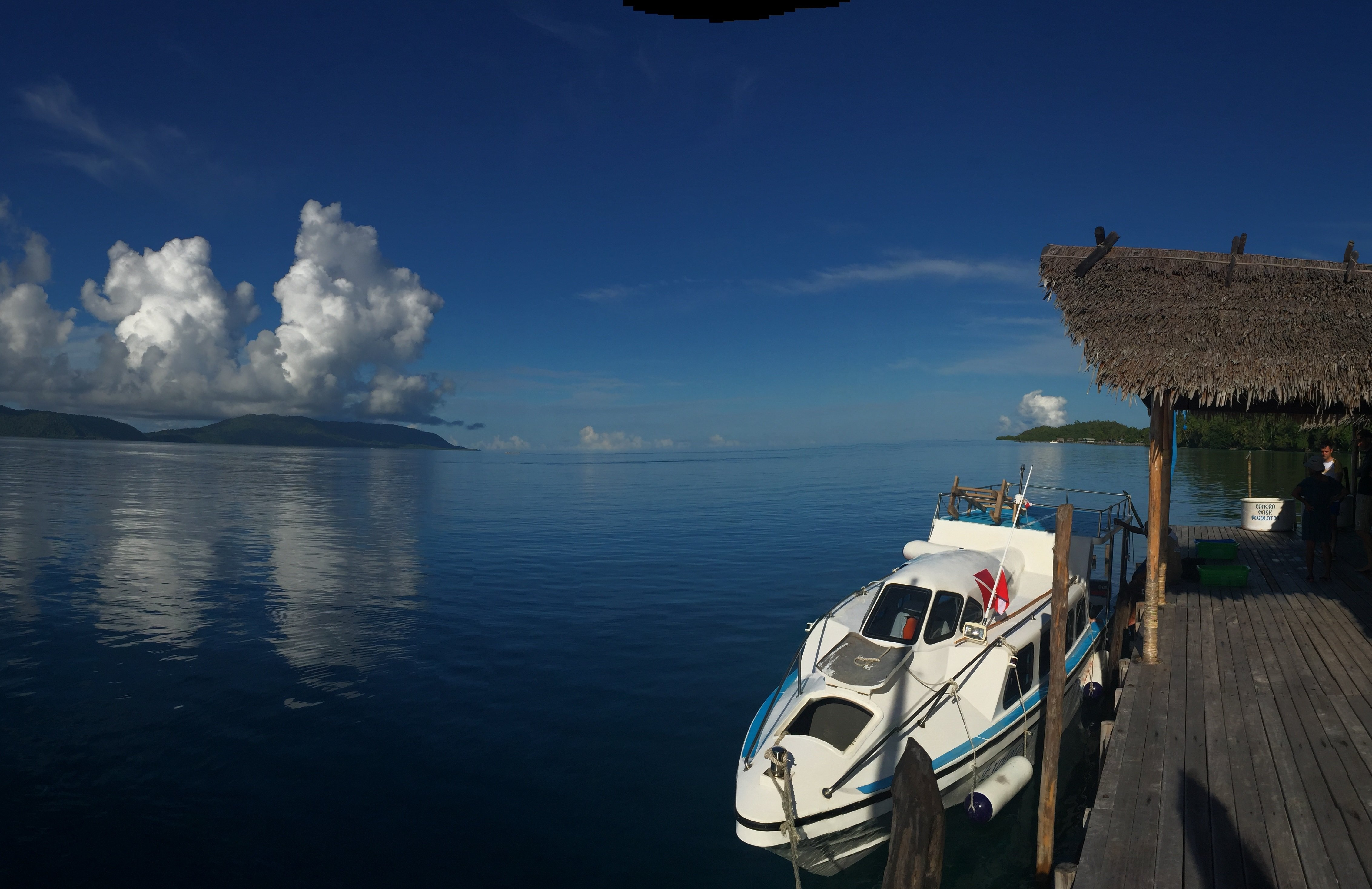 A Dive and Transfer Boat docked at our Raja Ampat Dive Center with islands of the Dampier Straight in the back