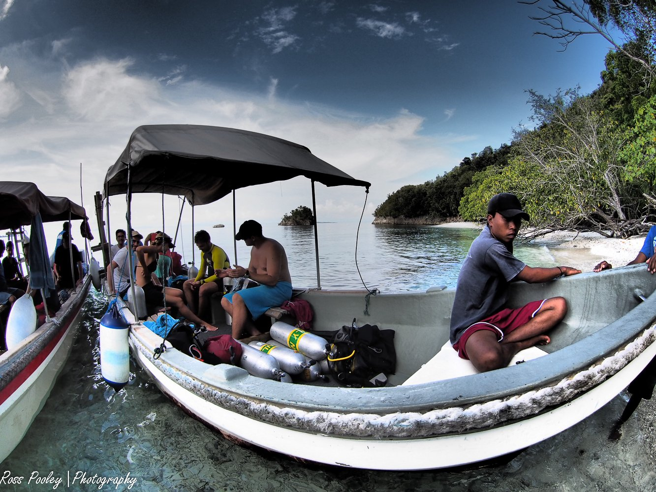guests and guides on two of our dive boats landing on a break in between dives on a white sanded Raja Ampat beach