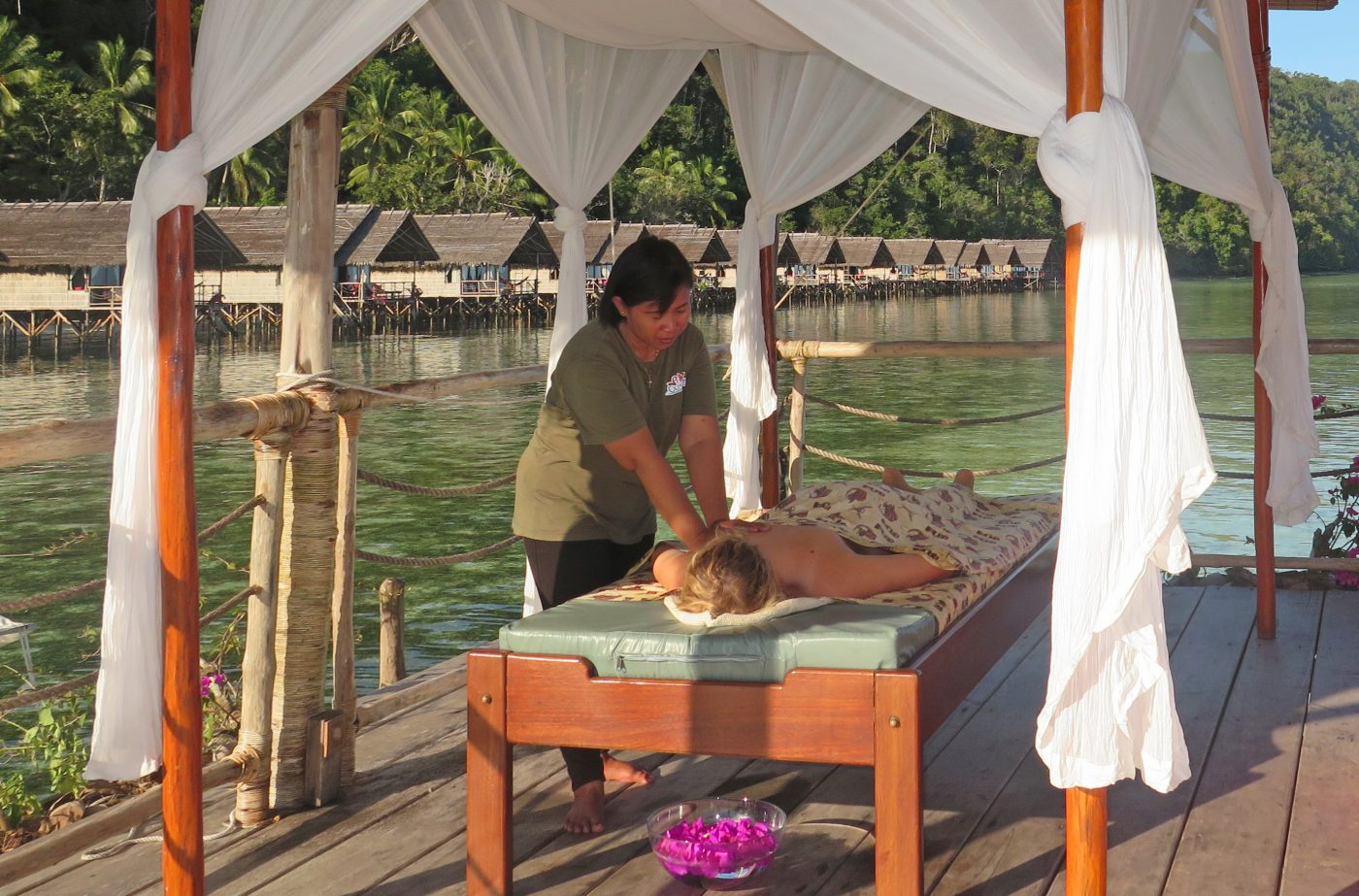 massage treatment with Papua Explorers bungalows in the background