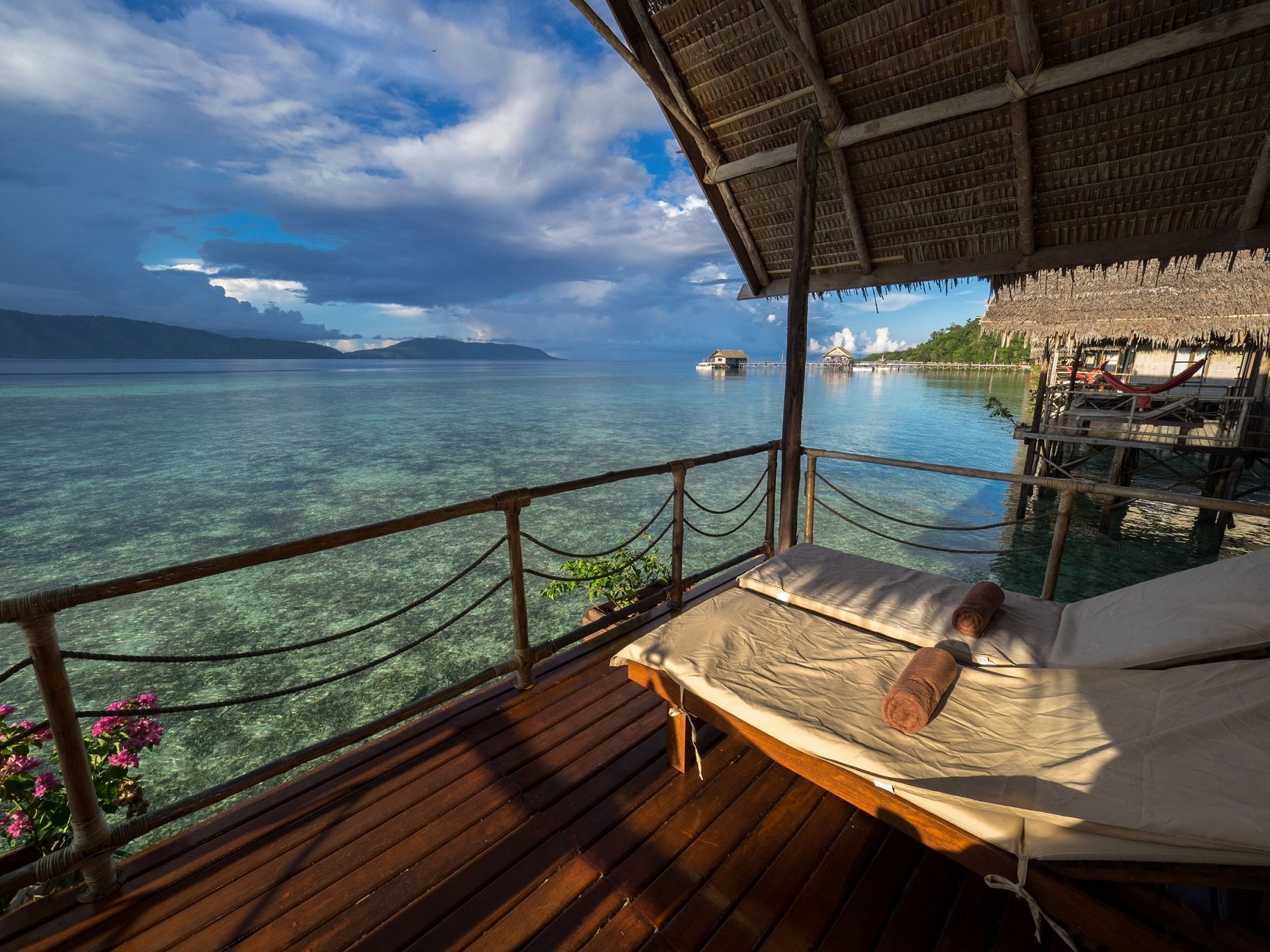 (English) view from the balcony of our water bungalows in Raja Ampat with sun loungers in the front and our dive centre and islands of the Dampier Straight in the back