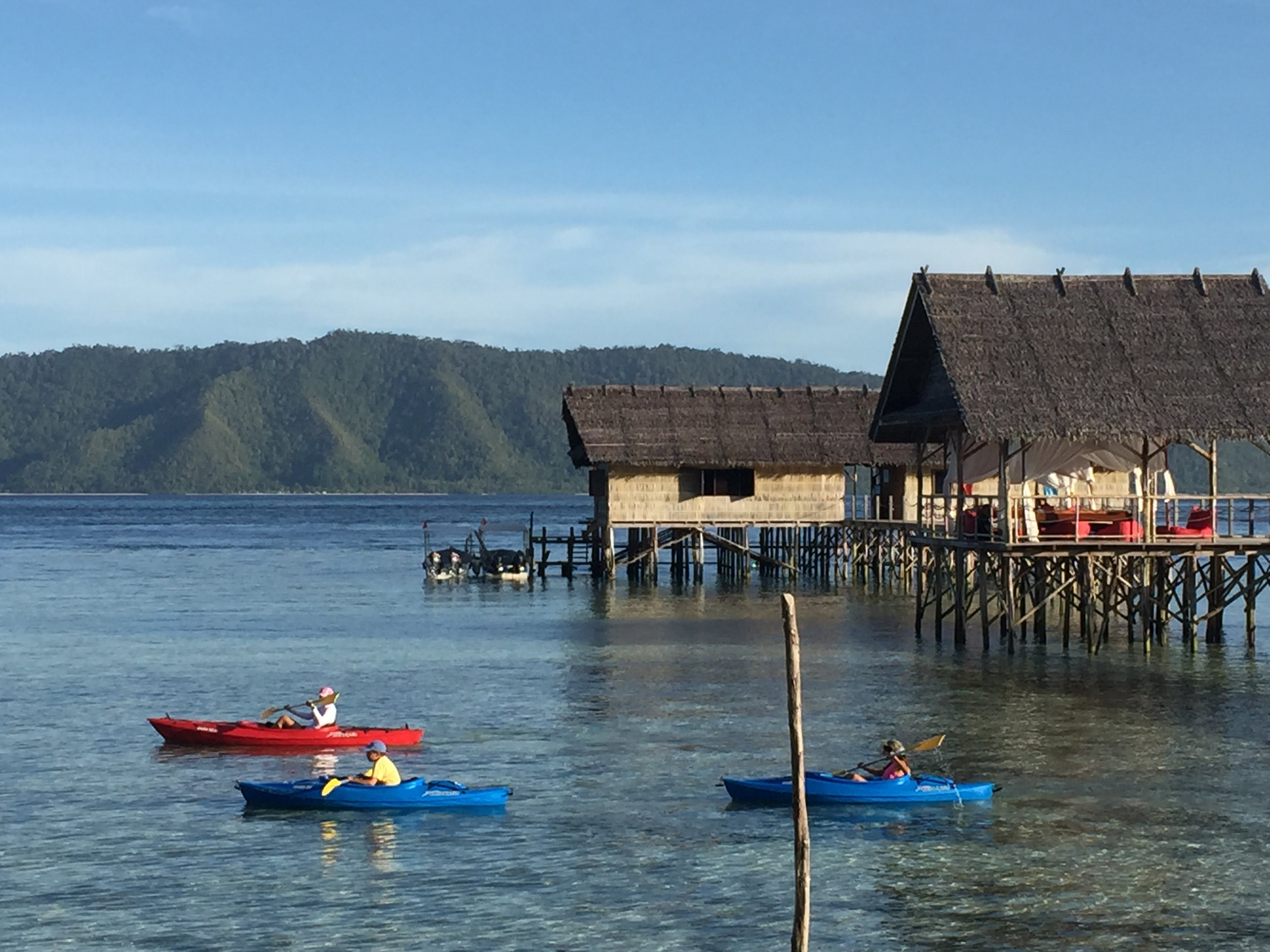 group of guests starting off for a kayak trip next to the jetty of our Raja Ampat dive resort