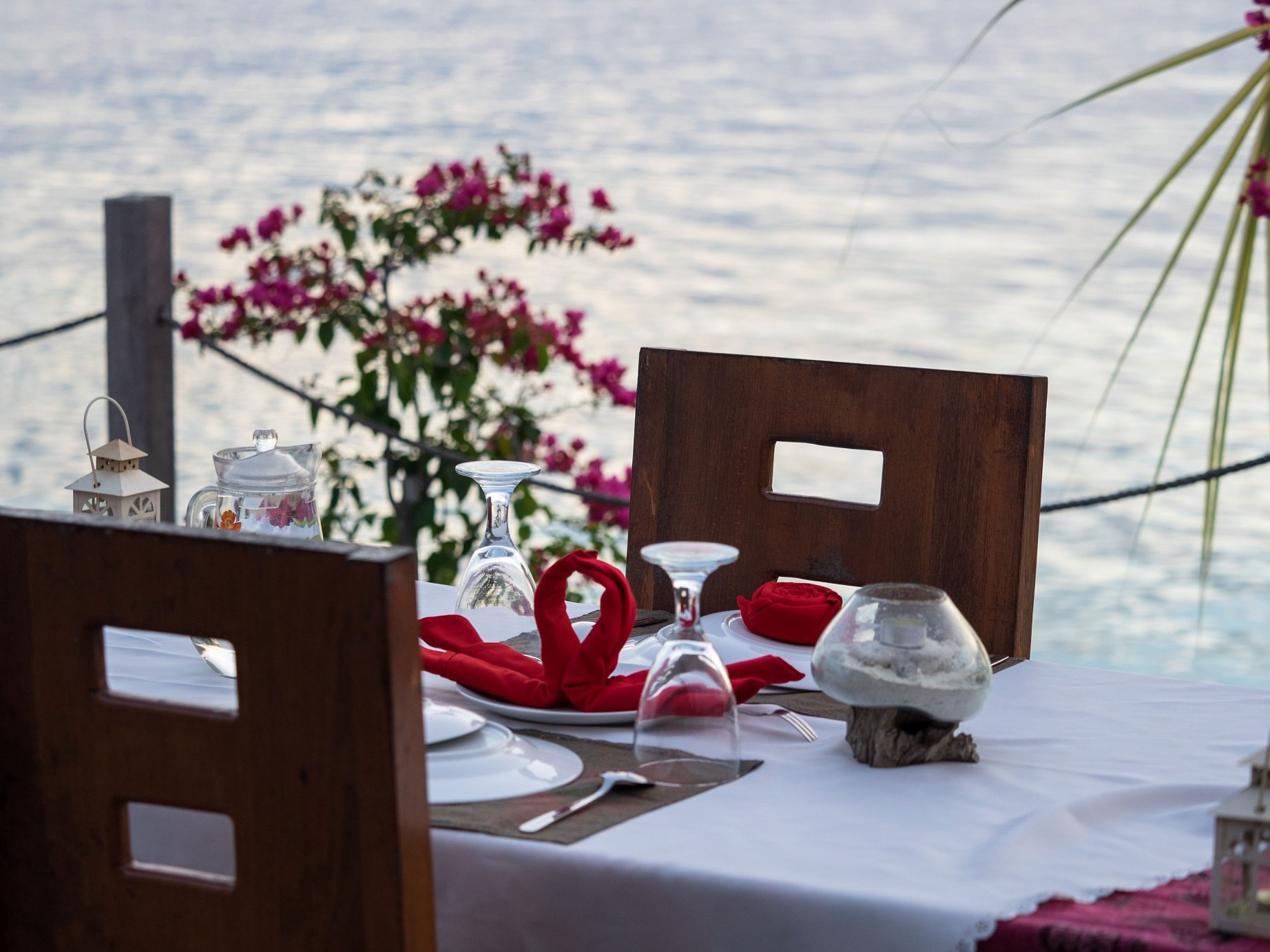 (English) table set up on the Papua Explorers sundeck for a couples dinner with flowers in the background