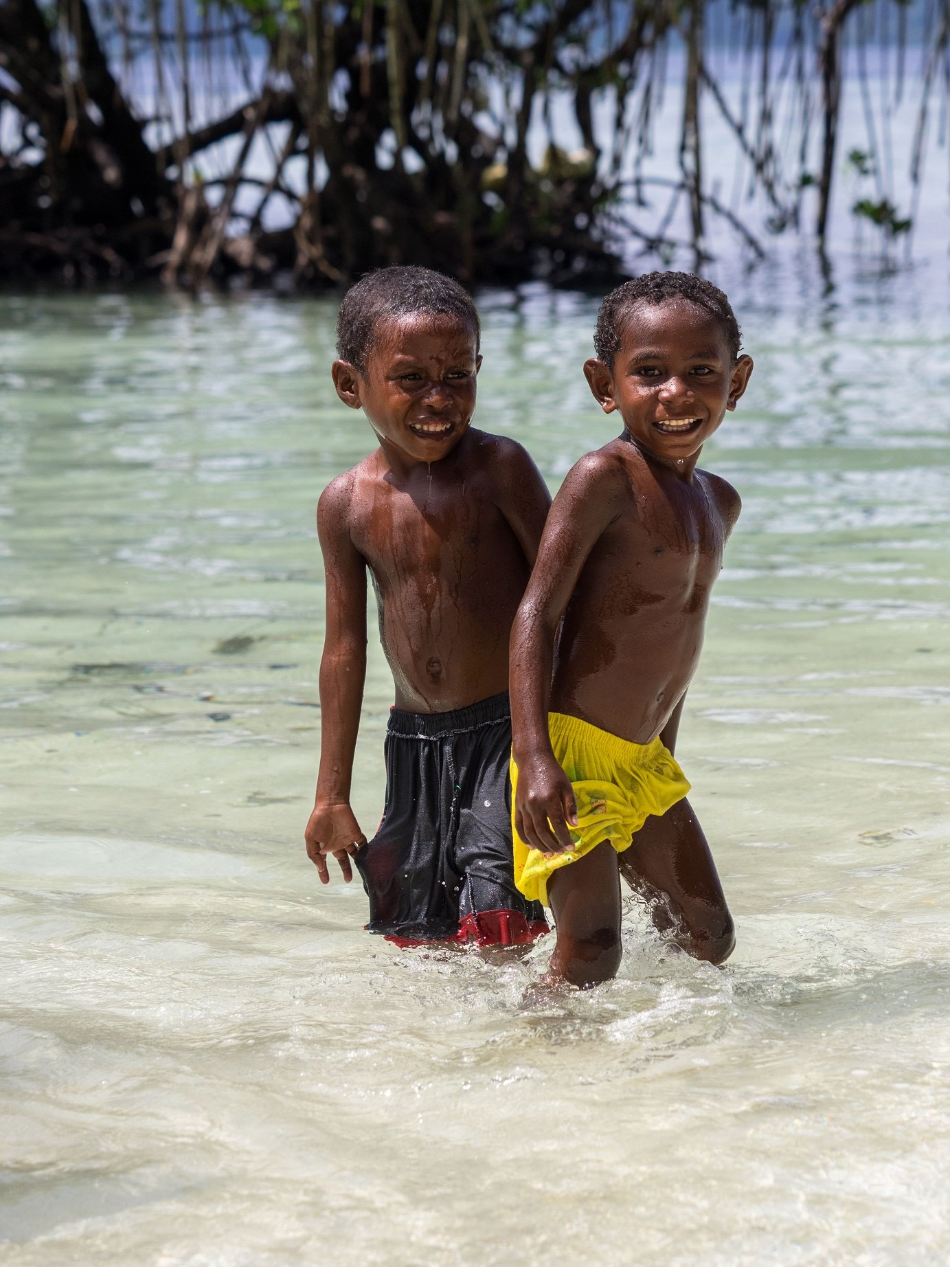 two local boys of Raja Ampat in swim shorts plashing in shallow water close to Papua Explorers Dive Resort