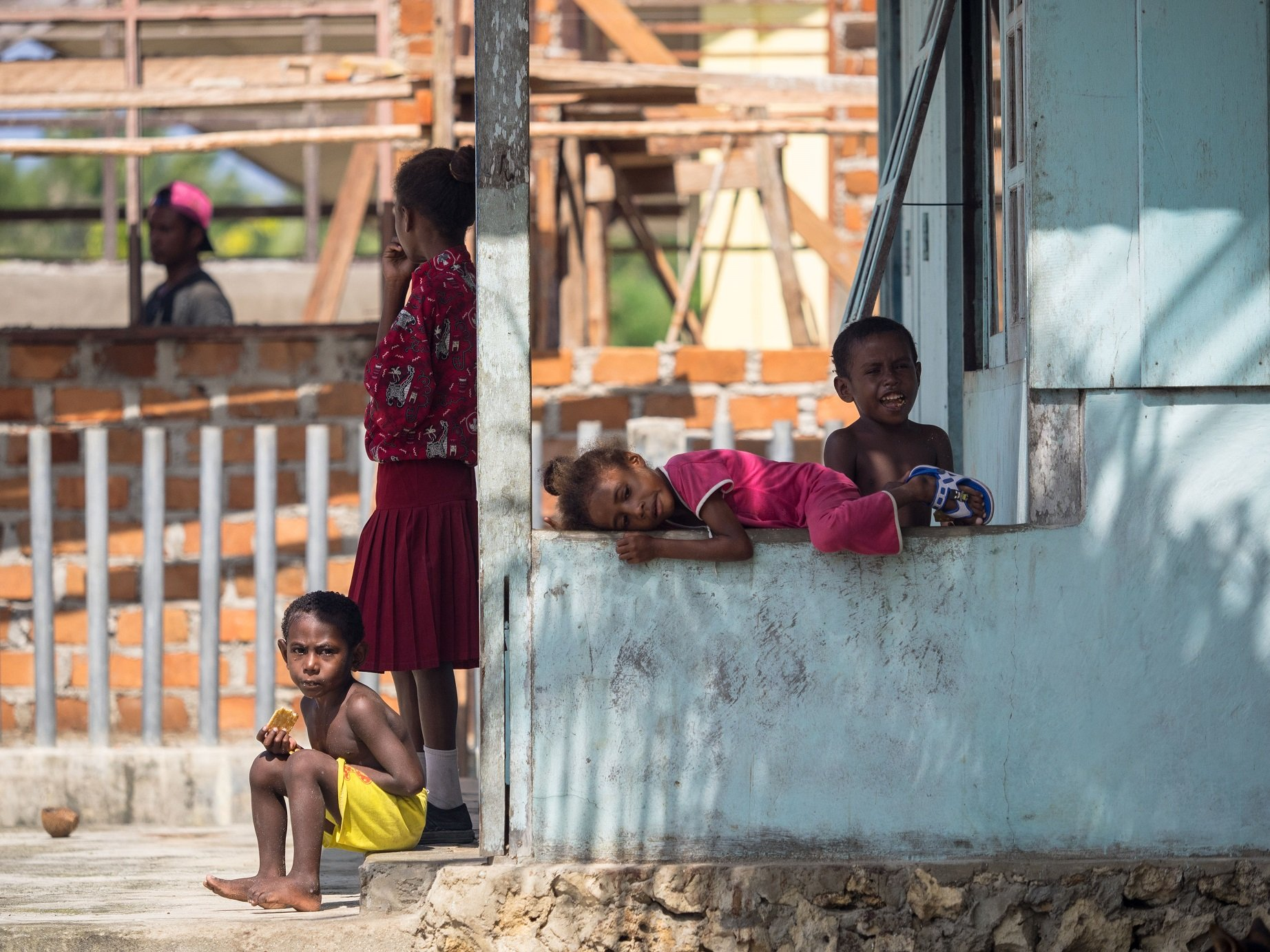 four local Papuan kids on the porch of their house in Yenwaupnor close to Papua Explorers Dive Resort