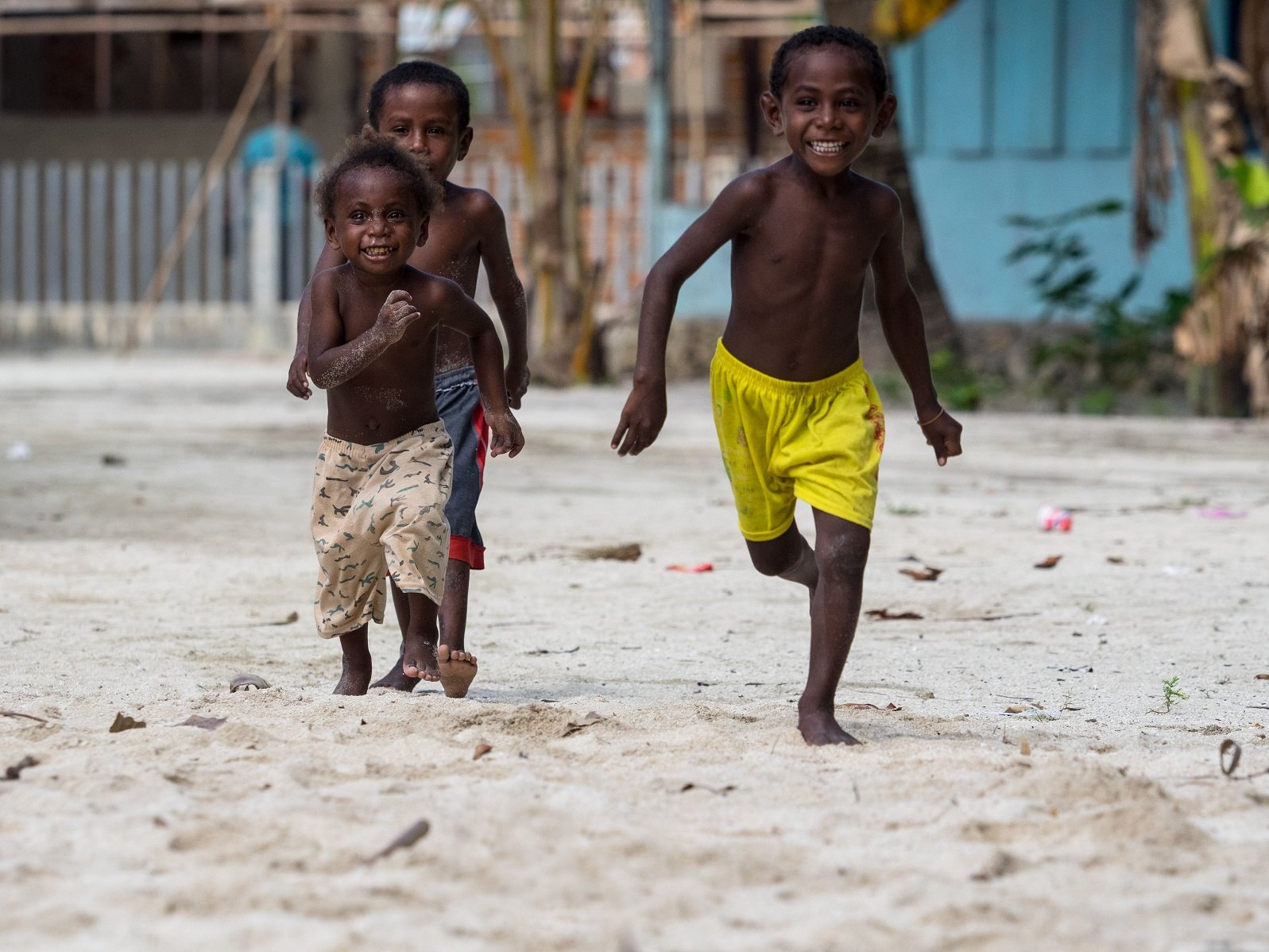 three happy Papuan kids running with village houses in the background