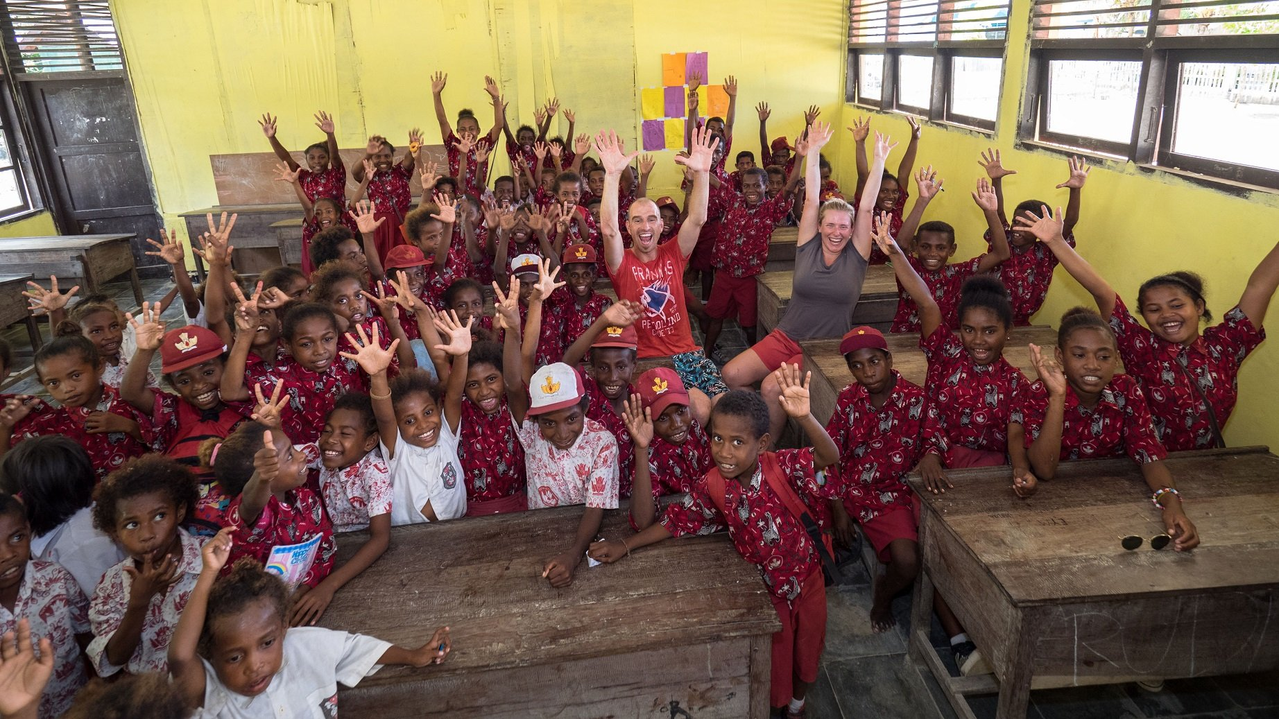classroom filled with local students wearing red batik school uniform at the neighbouring village of Papua Explorers Dive Resort