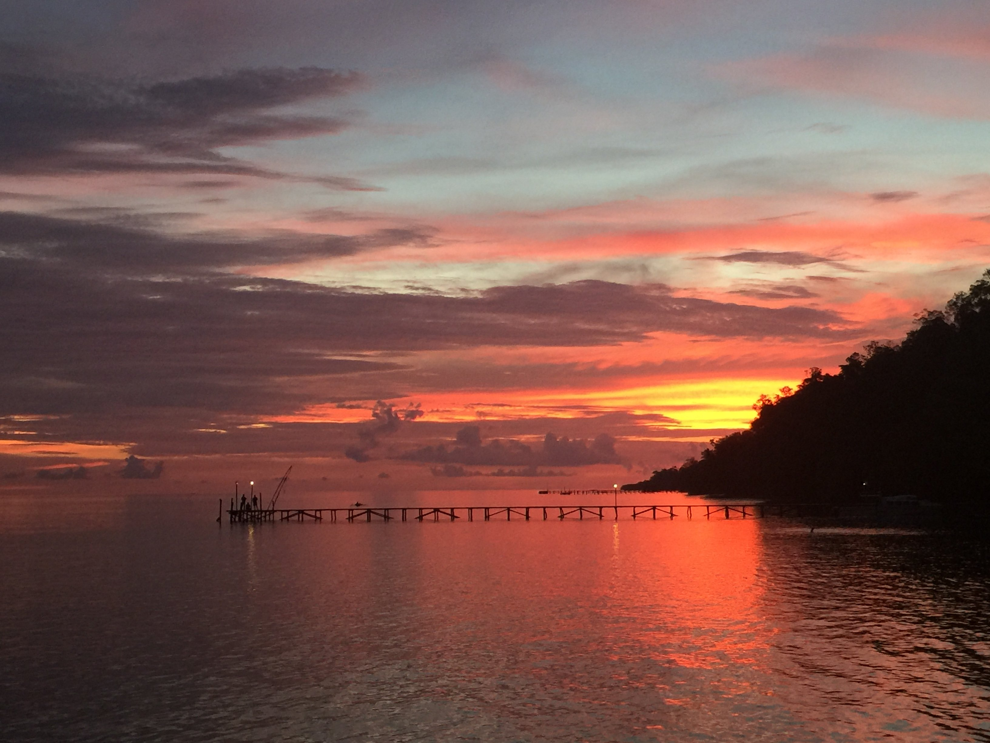 seascape and jetty under an orange red sky viewed from the sundeck of our dive resort in Raja Ampat