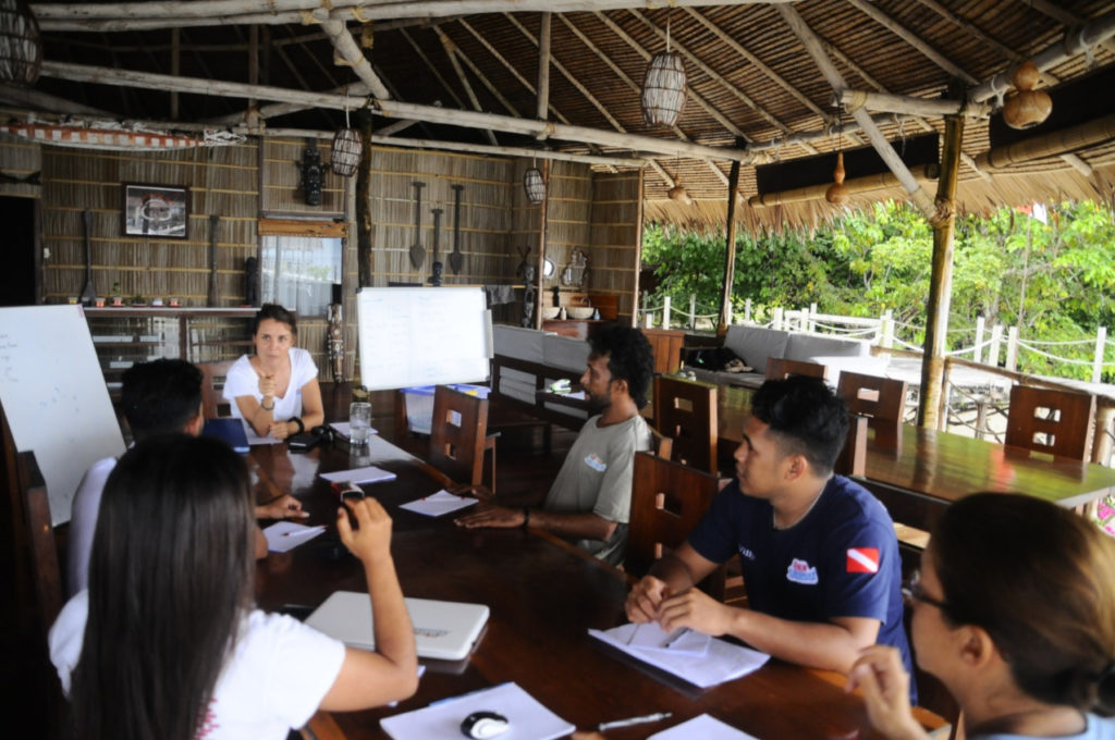 employees of Papua Explorers sitting at a table with the English teacher for class during Raja Ampat lockdown