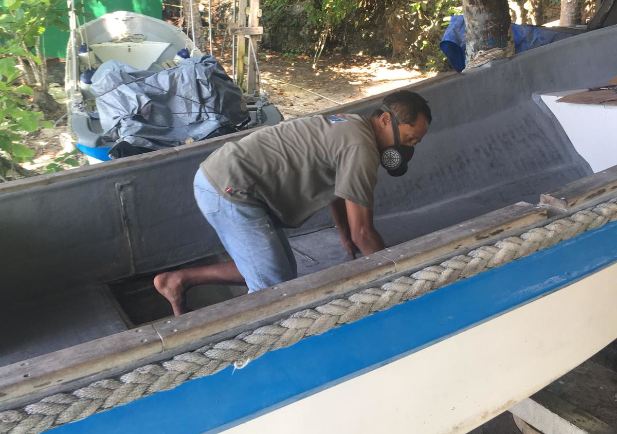 our fiberglass specialist shown inside a Papua Explorers boat during maintenance