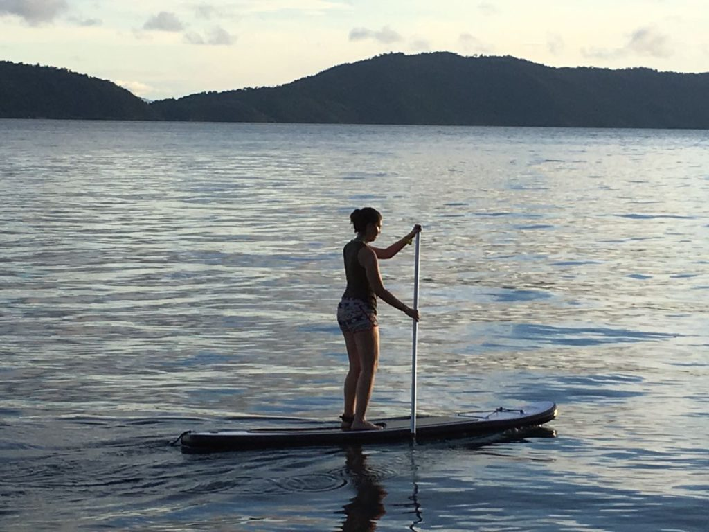 woman on a standup paddleboard with Raja Ampat islands in the background