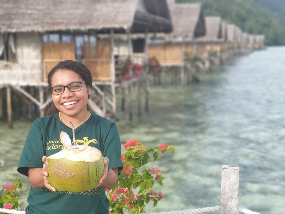 Papua Explorers staff member happily presenting young coconut drink with our water bungalows in the background