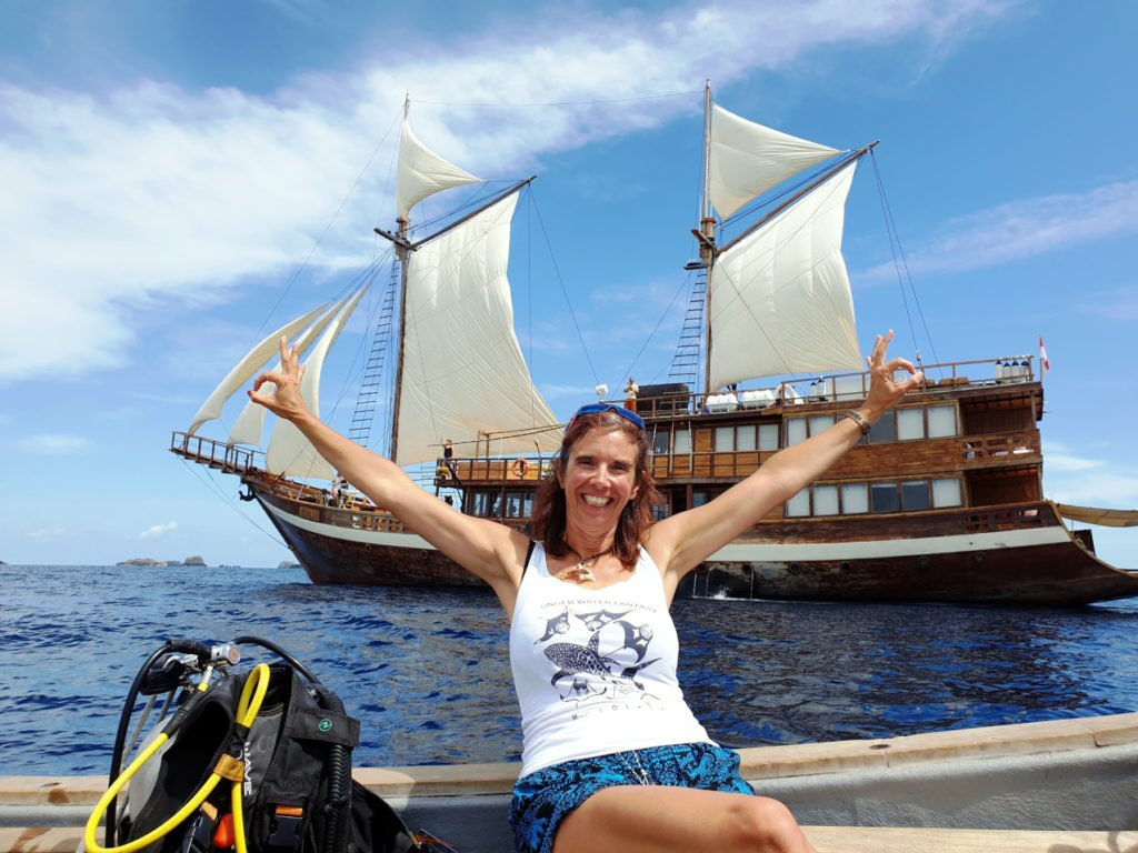 Papua Explorers Guest Gabby sitting on the tender with Coralia Liveaboard in the background