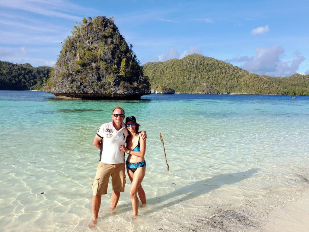 two Papua Explorers Returning Guests on a white sand beach at the Wayag Islands in Raja Ampat