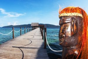 face of a wooden papuan statue with Papua Explorers main jetty in the backgound