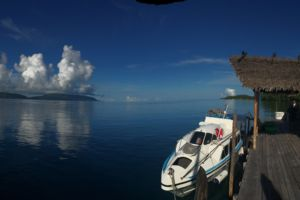 (English) A Dive and Transfer Boat docked at our Raja Ampat Dive Center with islands of the Dampier Straight in the back