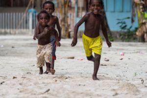 Village Kids of Raja Ampat running in the sand