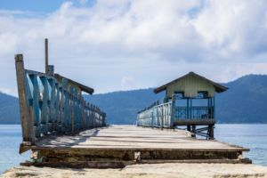 blue painted wooden jetty with two huts on the sides close to Papua Explorers Dive Resort