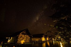 star-filled firmament above the well lit over water cottages of our Raja Ampat dive resort