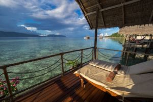 view from the balcony of our water bungalows in Raja Ampat with sun loungers in the front and our dive centre and islands of the Dampier Straight in the back
