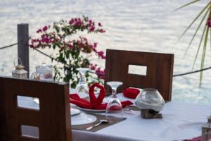 table set up on the Papua Explorers sundeck for a couples dinner with flowers in the background