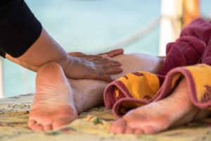 one of our massage specialists kneading the calves of a guest at the Papua Explorers Resort Spa