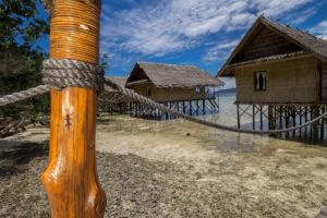 view of our water bungalows in our resort in Raja Ampat with a tiny gekko sitting on a jetty pillar in the front
