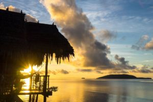 view of kri island and the sun rising above the sea shining through the veranda of one of our water cottages at our dive resort in Raja Ampat