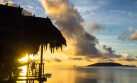 (English) view of kri island and the sun rising above the sea shining through the veranda of one of our water cottages at our dive resort in Raja Ampat