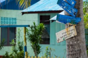 blue painted houses in Arborek with a colorful fence and a tree with signs reminding to treat the reefs with care observed on a break in between dives with Papua Explorers Dive Resort