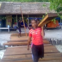 Papuan lady carrying jetty plank