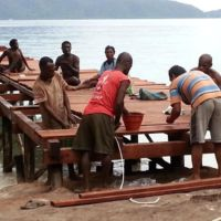 Construction team setting the main jetty planks at Papua Explorers